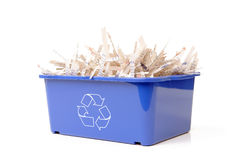 Paper recycling. Paper cuttings in blue plastic disposal bin with white recycle symbol - over white background Stock Image