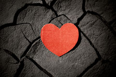 Paper red heart on cracked earth Stock Photos