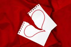 Paper with a red heart drawn torn to pieces on red silk fabric background. royalty free stock images