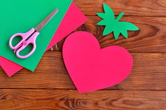 Paper red heart, paper green leaves on a wooden table Royalty Free Stock Photography