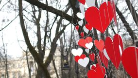 Paper red hearts decoration swaying on the wind  in the autumn park. Valentine's day concept.  stock video footage