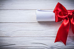 Paper roll with red knot on wooden board holidays concept Royalty Free Stock Images