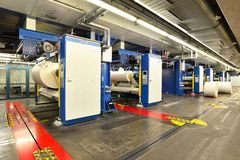 Paper rolls and offset printing machines in a large print shop f. Paper rolls and offset printing machines in a large print shop - closeup stock photo