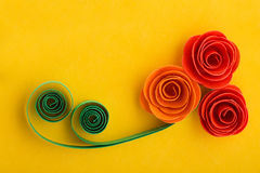 Paper rose flowers made with quilling technique on yellow background