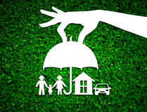 Paper salesman agent hand holding family protection on green Stock Images
