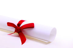 Paper scroll and red bow. Isolated on white backgrou royalty free stock photos