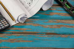 Paper scrolls, pencil, calculator and spirit level. On wooden plank Stock Photos