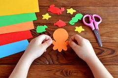Paper sea animals - octopus, fish, starfish, seahorse, crab. Child holds a paper octopus in hands. Kids diy Stock Photo