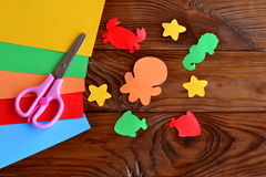 Paper sea animals - octopus, fish, starfish, seahorse, crab. Sheets of colored paper, scissors on wooden background Royalty Free Stock Photos