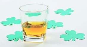 Paper Shamrocks. Glass of whisky and green shamrocks royalty free stock images