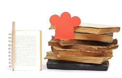 Blank notebook for your fine recipes. Paper shape chef hat on stack books and blank notebook for your recipes, menu Stock Image