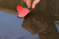 Paper shaped heart in water stream with hand Royalty Free Stock Photos