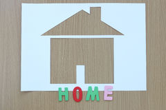 Paper shaped house on a background of brown wood and Craftsman t Royalty Free Stock Images