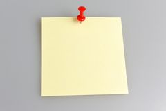 Paper sheet attached with office button on gray. One yellow paper sheet attached with red office button on gray background Royalty Free Stock Image