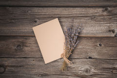 Paper sheet and dried lavender on old wooden background Stock Photos