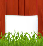 Paper sheet and green grass on wooden texture Royalty Free Stock Images
