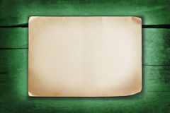 Paper sheet on a green painted cracked wood background. Ancient paper sheet with shabby corners on a green painted cracked wood background Royalty Free Stock Image