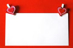 Paper sheet with heart shaped clips on red background Stock Image