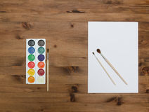 Paper sheet, palette with paint and brushes Royalty Free Stock Photos