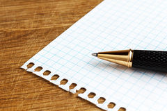 Paper sheet with pen on a wooden desk Royalty Free Stock Image