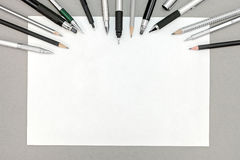 Paper sheet with pencils and pens on gray office desk Stock Photography