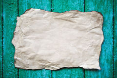 Paper sheet with shabby corners on a cracked wood Royalty Free Stock Photography