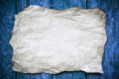 Paper sheet with shabby corners on a cracked wood Royalty Free Stock Photos