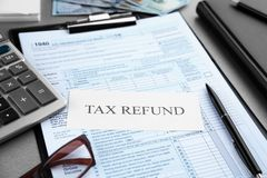 Paper sheet with text TAX REFUND and documents on table Royalty Free Stock Images