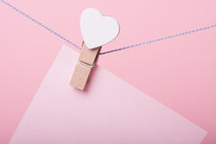 Paper sheet on thread. With heart shaped clothespin on rose background Royalty Free Stock Photos