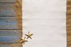Paper sheet and two starfish on planks and sand Royalty Free Stock Images