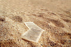 Paper sheets on golden sands. Macro view of two sheets of paper on a sandy beach royalty free stock photo