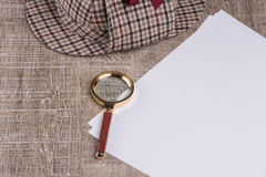 Paper sheets and magnifying glass Stock Images