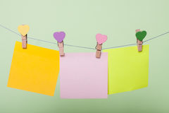 Paper sheets on thread. Colored paper sheets on thread with heart shaped clothespin on greenery background Stock Images