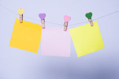 Paper sheets on thread. Colored paper sheets on thread with heart shaped clothespin on rose background Royalty Free Stock Photo