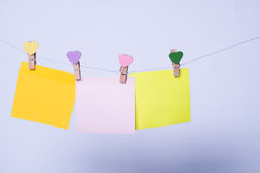 Paper sheets on thread. Colored paper sheets on thread with heart shaped clothespin on rose background Royalty Free Stock Photos