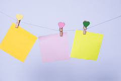 Paper sheets on thread. Colored paper sheets on thread with heart shaped clothespin on rose background Stock Photography