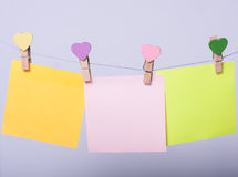 Paper sheets on thread. Colored paper sheets on thread with heart shaped clothespin on serenity background Stock Image