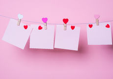 Paper sheets on thread. With heart shaped clothespin on rose background Stock Images