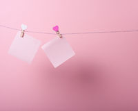 Paper sheets on thread. With heart shaped clothespin on rose background Stock Photo