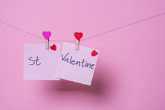 Paper sheets on thread. With heart shaped clothespin on rose background Stock Photos
