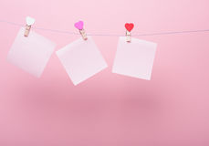Paper sheets on thread. With heart shaped clothespin on rose background Royalty Free Stock Photos