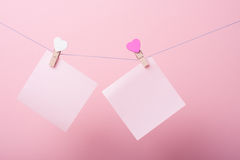 Paper sheets on thread. With heart shaped clothespin on rose background Royalty Free Stock Image