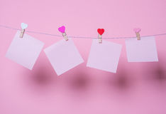 Paper sheets on thread. With heart shaped clothespin on rose background Stock Photography