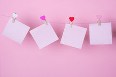Paper sheets on thread. With heart shaped clothespin on rose background Royalty Free Stock Images