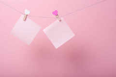 Paper sheets on thread. With heart shaped clothespin on rose background Royalty Free Stock Photo