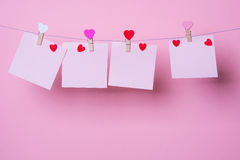 Paper sheets on thread. With heart shaped clothespin on rose background Royalty Free Stock Photography