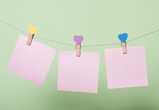 Paper sheets on thread. Serenity paper sheets on thread with heart shaped clothespin on greenery background Stock Photos