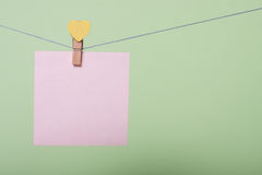 Paper sheets on thread. Serenity paper sheet on thread with heart shaped clothespin on greenery background Royalty Free Stock Photos