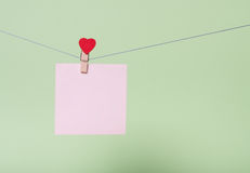 Paper sheets on thread. Serenity paper sheet on thread with heart shaped clothespin on greenery background Stock Photography