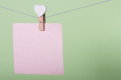 Paper sheets on thread. Serenity paper sheet on thread with heart shaped clothespin on greenery background Royalty Free Stock Photo